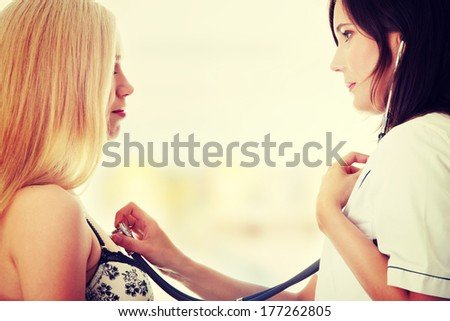 Young female doctor examinating with female patient.  - stock photo