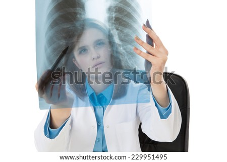 Young female doctor examining an x-ray image - stock photo