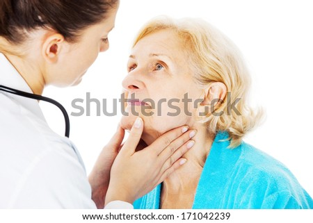 Young female doctor examining senior woman's throat isolated over white background - stock photo