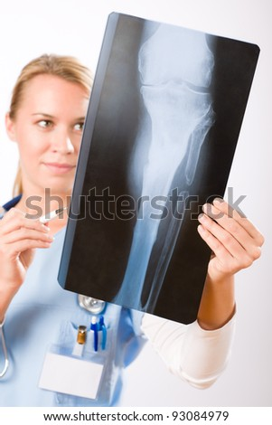 Young female doctor examining x-ray isolated on white background - stock photo