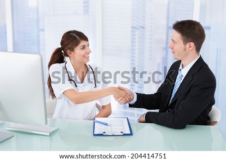 Young female doctor greeting businessman at desk in clinic - stock photo