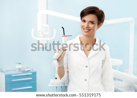 Young female doctor in dentist office.Beautiful smiling woman in white lab coat holding blue dental curing light.Dental clinic.Stomatology
