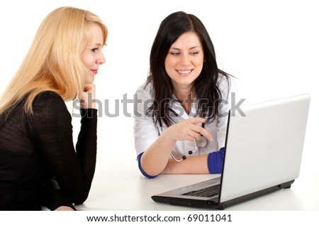 young female doctor in white uniform with patient looking at laptop - stock photo