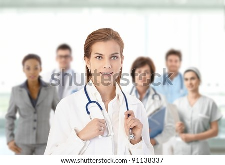 Young female doctor looking at camera, smiling, in front of medical team.?