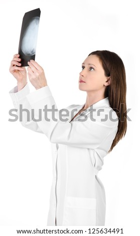 Young female doctor looking at the x-ray picture of head isolated on white background - stock photo