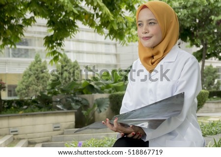 Young female doctor looking at the x-ray picture of lungs.