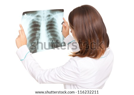 Young female doctor looking at the x-ray picture of lungs isolated on white background - stock photo