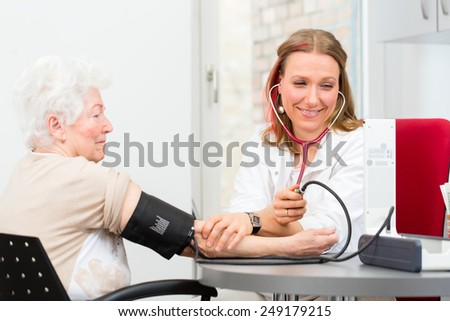 Young female doctor measuring blood pressure of senior patient in surgery consultation hour  - stock photo