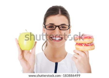 Young female doctor, nurse holding an apple and doughtnuts. Isolated on white.