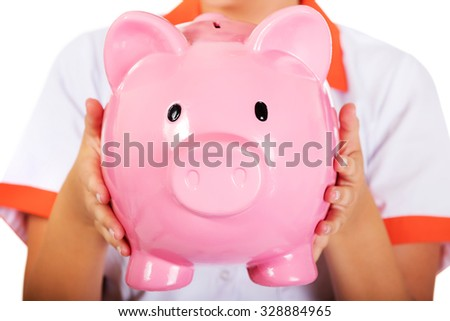 Young female doctor or nurse holding a piggybank.