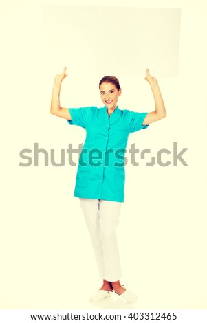 Young female doctor or nurse holding empty banner - stock photo