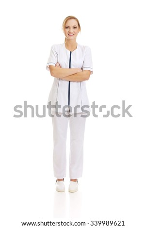 Young female doctor or nurse with folded arms. - stock photo