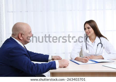 Young female doctor receiving patient in her office - stock photo