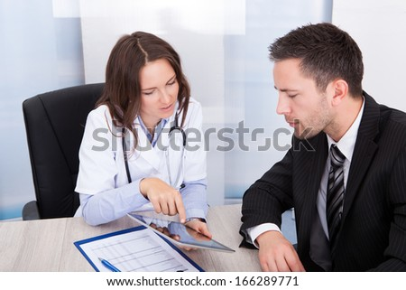 Young Female Doctor Showing Digital Tablet To Businessman - stock photo