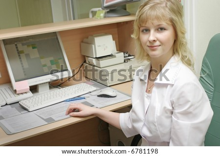 Young female doctor sits by desk in doctor's office. - stock photo
