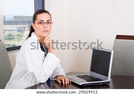 young female doctor sitting by her laptop computer - stock photo
