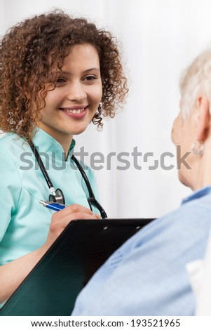 Young female doctor talking with elderly woman - stock photo