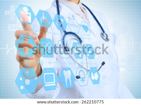 Young female doctor touching icon of media screen - stock photo