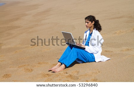 young female doctor using laptop on beach - stock photo