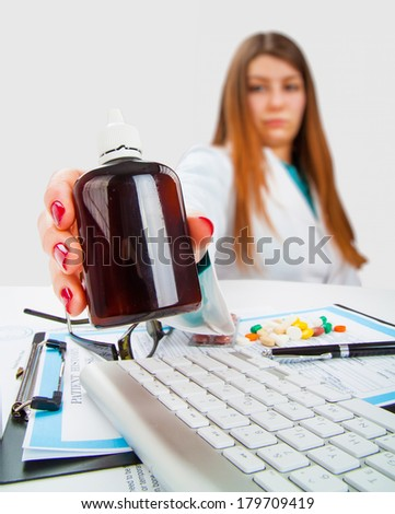 Young female doctor with bottle of pills in her hand