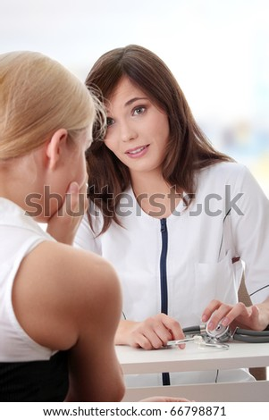 Young female doctor with female patient. - stock photo