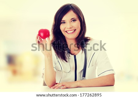 Young female doctor with heart in her hand.