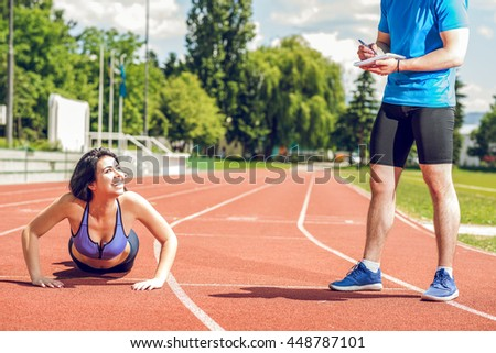 Young female doing push ups exercise outdoor on athletics sport track during hot summer day with help of her personal trainer. - stock photo
