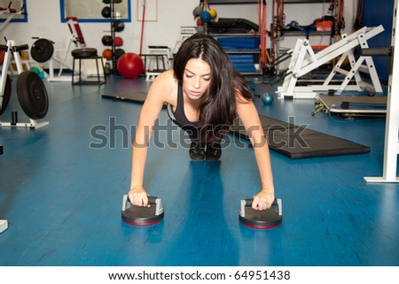 young female doing push ups in the gym - stock photo
