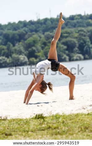 Young female doing yoga at the beach.