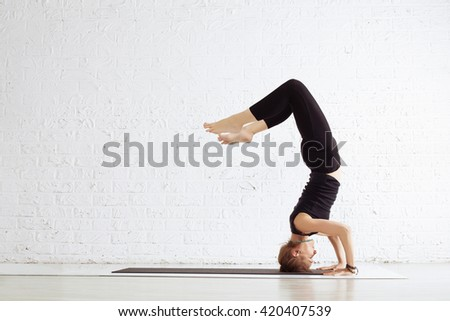 Young female doing yoga exercise headstand in studio. Individual Sport activity, relaxation - stock photo