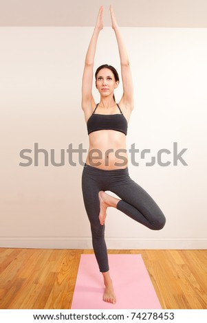 Young female doing yoga indoors