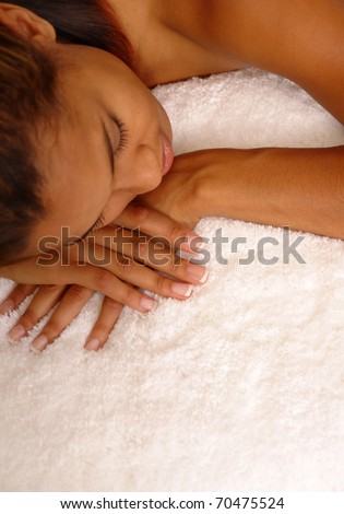 young female dozes off for a nap on plush white carpet.
