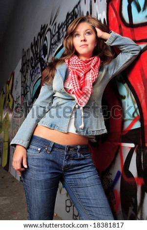 young female dressed in jeans jacket pose in front of graffiti - stock photo