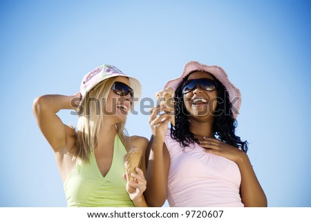 young female dressed in summer clothing eating ice-cream and having fun - stock photo