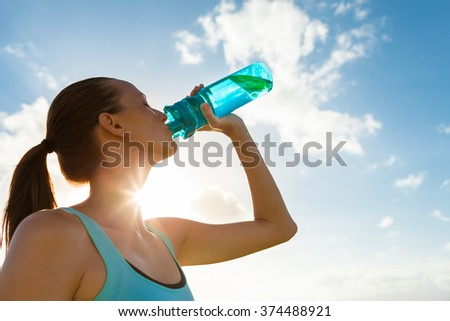 Young female drinking a bottle of water.