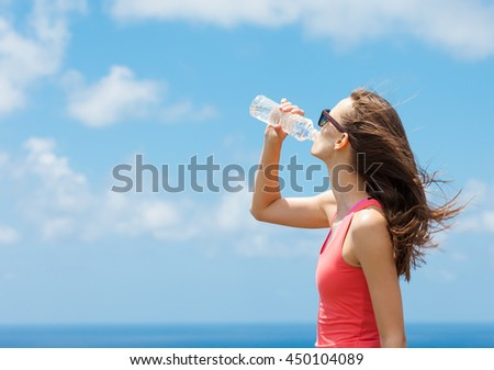 Young female drinking water.