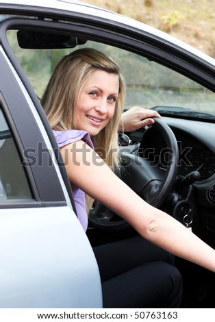 Young female driver at the wheel in her new car - stock photo