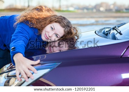 Young female driver embracing hood of new car - stock photo