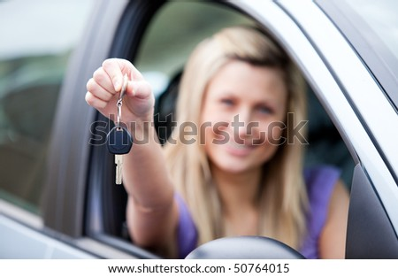 Young female driver holding a key after buying a new car - stock photo
