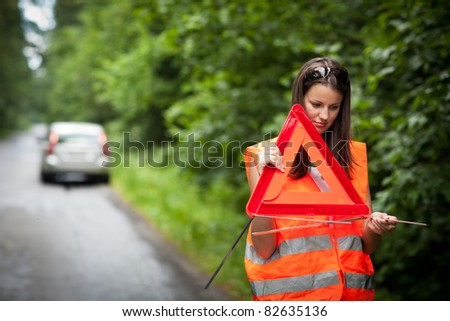 Young female driver wearing a high visibility vest/safety vest, putting in place the warning triangle after her car has broken down - stock photo
