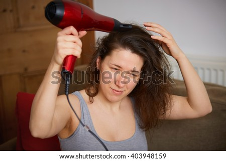 Young female dry her hair with red hair dryer - stock photo