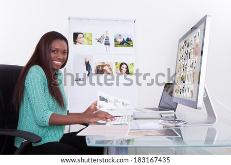 Young female editor using digital tablet at photo agency - stock photo
