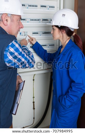 young female electrician worker using a fuse board