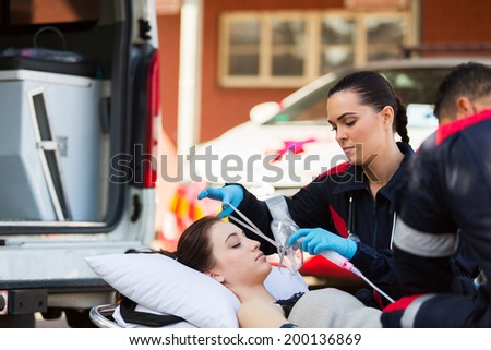 young female EMT putting oxygen mask on unconscious patient - stock photo