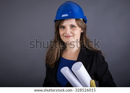 Young female engineer holding blueprint, concept of successful construction, over gray background - stock photo