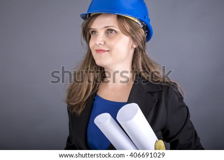 Young female engineer holding blueprint, concept of successful construction, over gray background