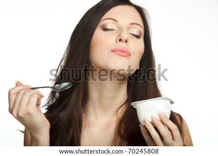 Young female enjoying taste of yogurt isolated on white - stock photo