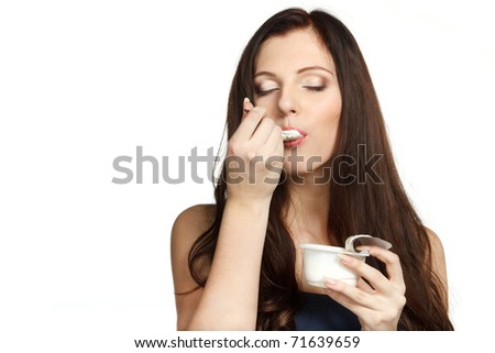 Young female enjoying taste of yogurt isolated on white - stock photo