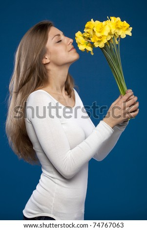 Young female enjoying the smell of flowers on blue background, side view - stock photo