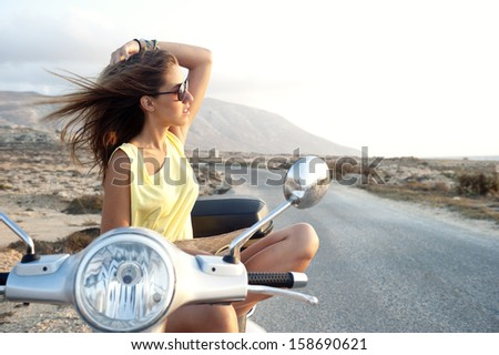 Young female enjoys a motorcycle trip and admires the view - stock photo